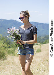 Girl in the field with bouquet made of natural mountain flowers surrounded by mountains on a hiking trip