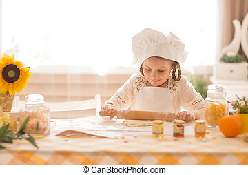 girl in the form of a cook rolls out the dough in the kitchen
