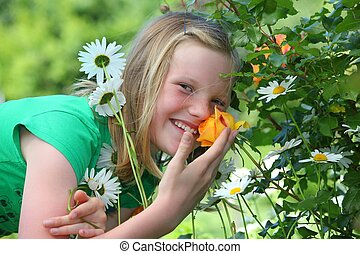 Girl in the garden - A young blonde girl takes a smell at an...
