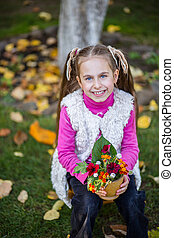 Girl in the garden with an autumn bouquet of flowers on a background of green grass.