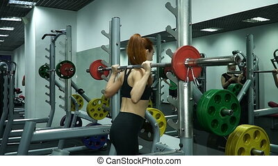 Girl in the gym. Exercise with a barbell