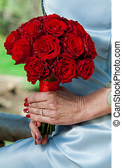 girl in the hand is holding a bouquet of red roses