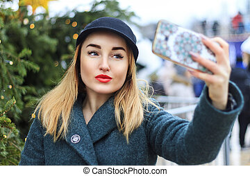 girl in the hat makes selfie smartphone for under the Christmas tree