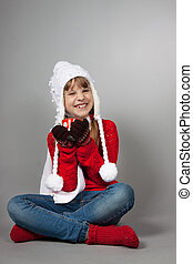 girl in the hat of Santa Claus with a cup