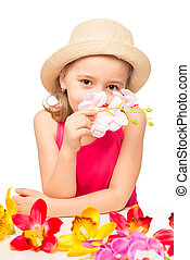 girl in the hat smelling a branch of pink orchids on a white background