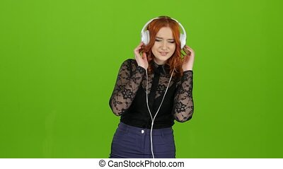Girl in the headphones is listening to music. Green Screen