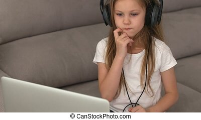girl in the headphones looks with interest at the laptop screen. Distance learning, school online. High quality 4k footage