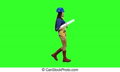 Girl in the helmet with construction tools on the waist goes sideways on a green background