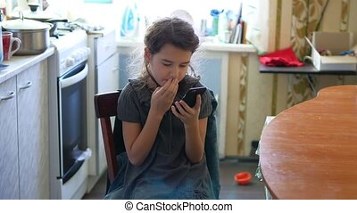 Girl in the kitchen playing smartphone online games breakfast