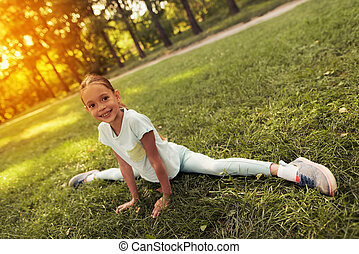 Girl in the park sits on a string. She smiles