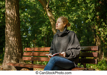 girl in the park with a book