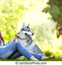 girl in the park with a Husky dog