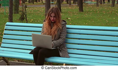 girl in the Park works with the laptop