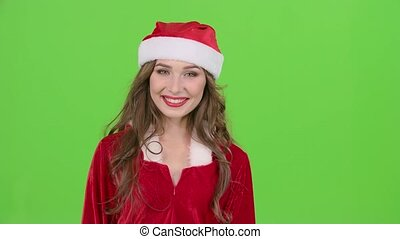 Girl in the red suit of the snow maiden winks and shows her finger ok. Green screen. Close up