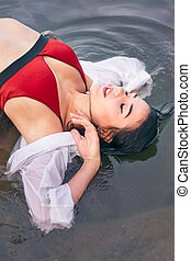 girl in the river on a stone in a red swimsuit one