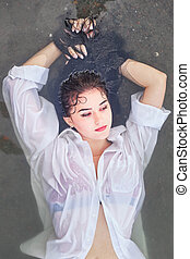girl in the river on a stone in a white shirt, top view