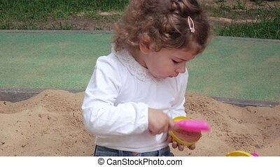 Girl in the sandbox - Girl in formal attire playing in the...