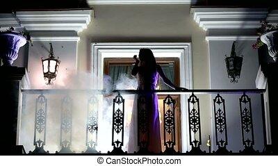 Girl in the smoke on the balcony
