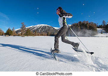 Girl in the snow runs with snowshoes