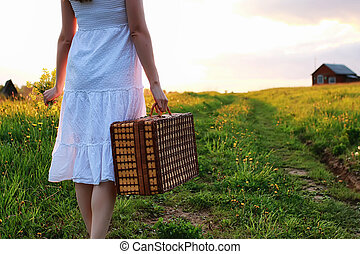 Girl in the spring in the field. A girl with a suitcase walks th
