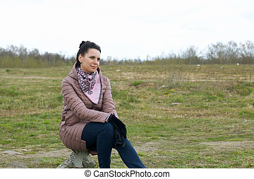 Girl in the spring meadow. Sits on a stone. Dressed in a spring jacket, a scarf around her neck.