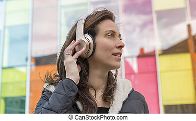 girl in the street listening to music with headphones on her head, she wears a long hair to the wind and winter jacket