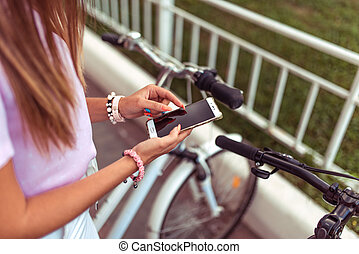Girl in the summer in the city in hand phone, choice of route, background of the parking bicycles. Online application for renting bicycles. Female hands smartphone manicure bracelets and long hair.