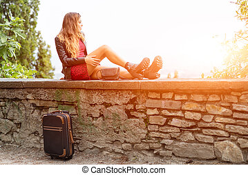 Girl in the sun on a wall with suitcase waiting.