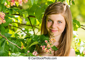Girl in the sunshine smelling tree blossom