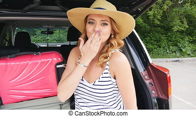 Girl in the trunk of a car with suitcases