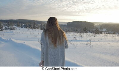 Girl in the winter forest at sunset