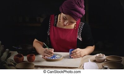 Girl in traditional national dress paints pottery