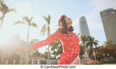 Girl in traditional Vietnamese dress spinning happy with yellow flowers. Downtown Da Nang city.