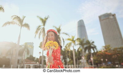 Girl in traditional Vietnamese dress spinning happy with yellow flowers. The mood of delight.