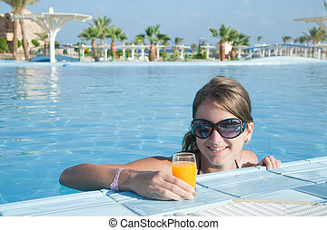 Girl in tropical pool with orange juice