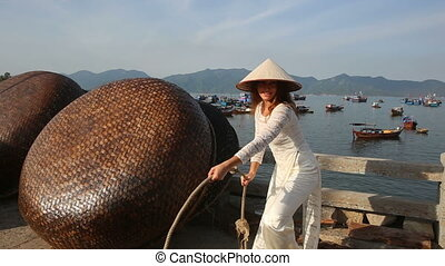 girl in vietnamese plays with handmade boats on embankment