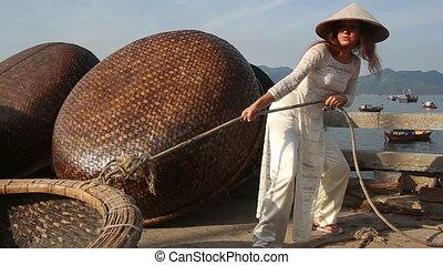 girl in vietnamese pulls ripe of handmade boat on embankment
