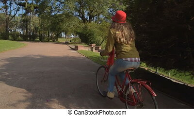Girl in vintage fashion riding bike at the park