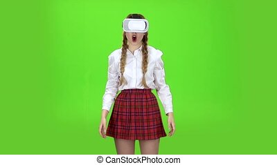 Girl in virtual reality glasses is watching an exciting video Green screen. Slow motion