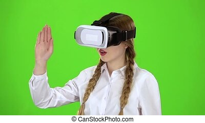 Girl in virtual reality glasses is watching an exciting...