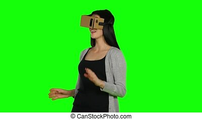 Girl in virtual reality is smilling and it makes him laughing. Green screen