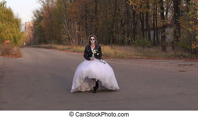 Girl in wedding dress with a skull mask on her face is running on an empty road