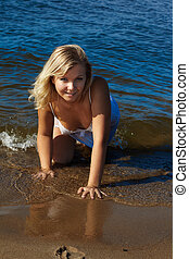 beautiful blonde girl posing in wet peignoir in the waters of sea