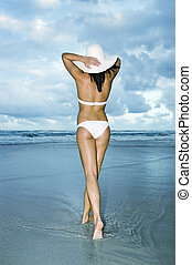 Girl in white bikini walking on beach with white sun hat -...