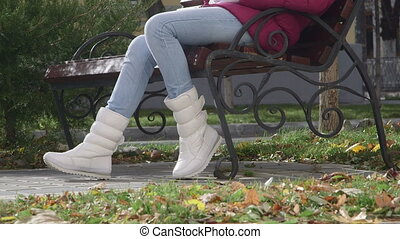 Girl in white boots sitting on a bench in autumn