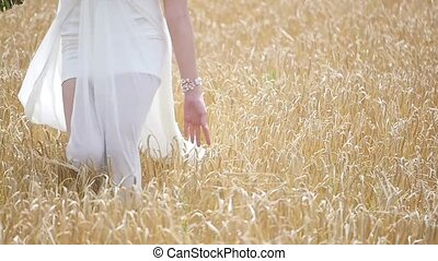 girl in white dress in the wind, walking through a field of wheat. . slow motion.
