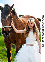 Girl in white dress leading horse.