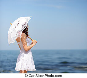 Girl in white dress on a sea beach, hiding from sun with umbrella