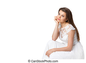 girl in white dress sitting looking at the camera