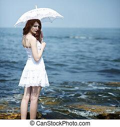Girl in white dress standing near sea with lace sun umbrella